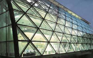 массивная сетчатая оболочка из стальных труб со сварными узлами поддерживает фасадное остекление, которое выполнено из треугольных сегментов, дублирующих ячейки оболочки